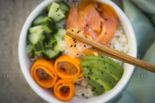 Sushi-Bowl with salmon- cucumber- avocado- rice and carrot- salmon and chopsticks in the foreground