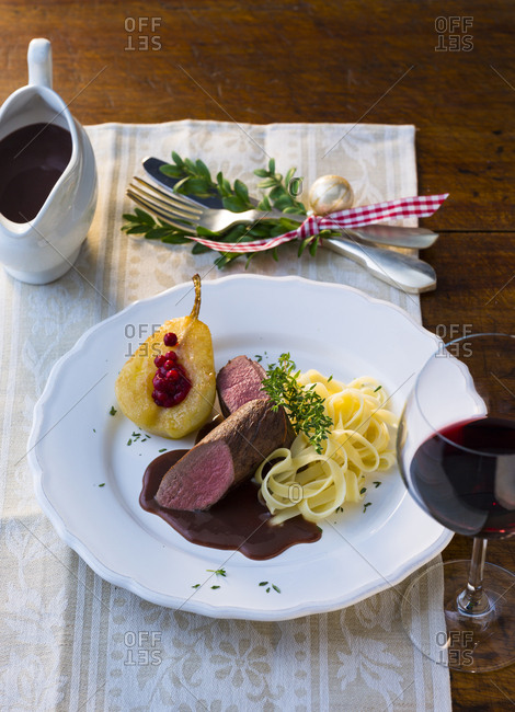 Plate of venison filet with ribbon noodles- stuffed pear and red wine sauce