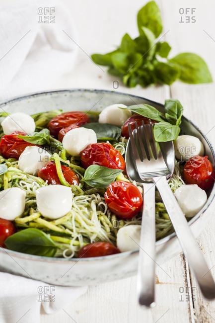 Zoodles Caprese- spiralized zucchini- glass noodles- pesto- plum tomato- mozzarella balls