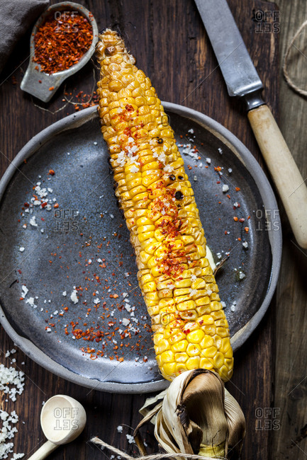 Grilled corncob with butter- salt and chili flakes on plate