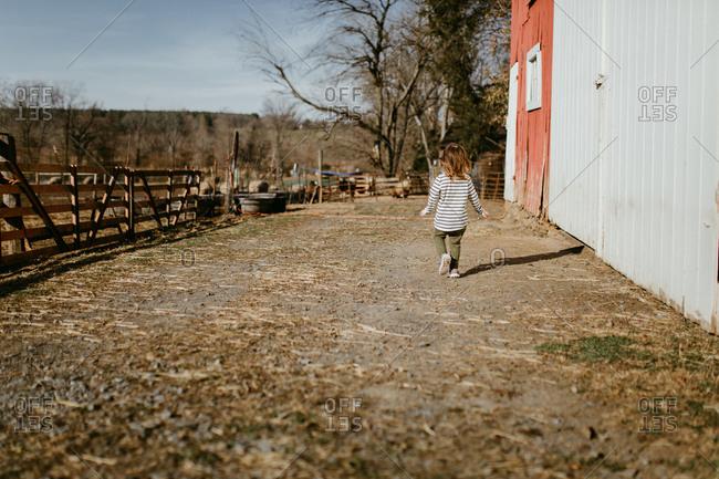 Child walking alongside barn - Offset