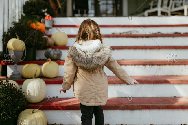 Girl wearing winter coat walking up steps decorated with pumpkins