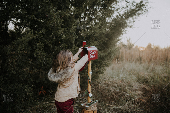 Girl reaching into mailbox to send a letter to Santa