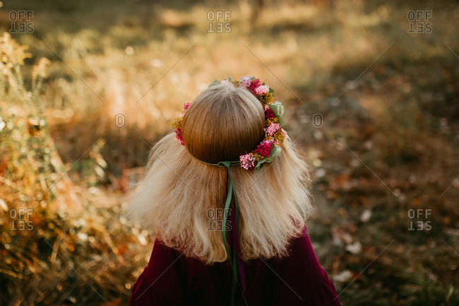 Girl with blond hair wearing a headband made from wildflowers
