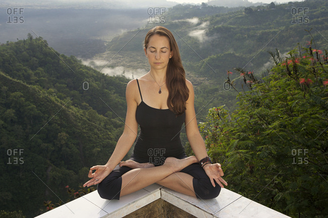 Meditating woman in lotus position on edge of balcony overlooking tropical rainforest