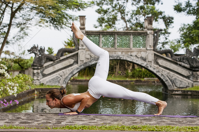 Woman practicing yoga in a scenic park in Bali