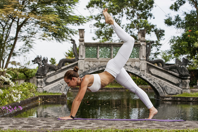 Woman practicing yoga in park with pond and bridge in Bali