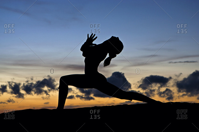 Silhouette of a woman in a yoga pose at sunset
