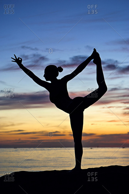 Silhouette of a young woman practicing yoga at the beach at sunset