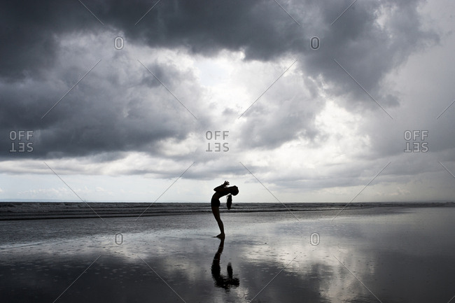 Silhouette of a young woman practicing yoga at the beach in Bali