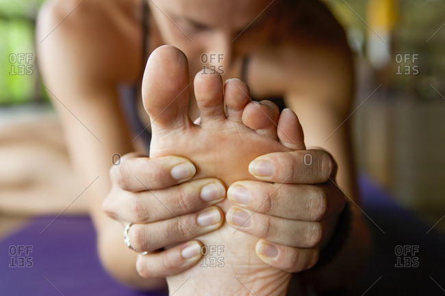 Woman stretching and touching her bare foot in yoga pose