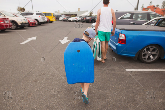 Father and son carrying chairs and a boogie board in a parking lot