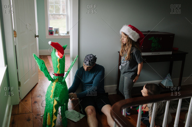 Kids watch while dad sets up a Christmas dragon