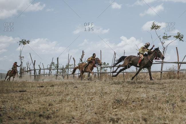 Indonesia, Sumbawa Besar - September 16, 2017: Low angle view of jockeys riding racehorses against sky during horse racing