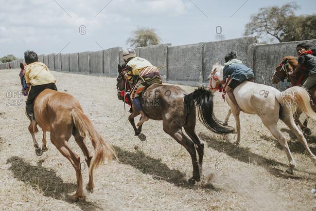 Indonesia, Sumbawa Besar - September 16, 2017: Rear view of jockeys riding racehorses during horse racing
