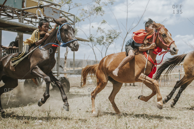 Indonesia, Sumbawa Besar - September 16, 2017: Side view of jockeys riding racehorses during horse racing