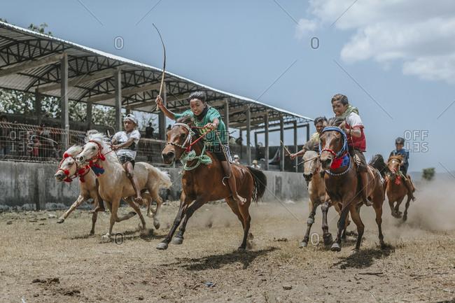 Indonesia, Sumbawa Besar - September 16, 2017: Children riding racehorses during horse racing