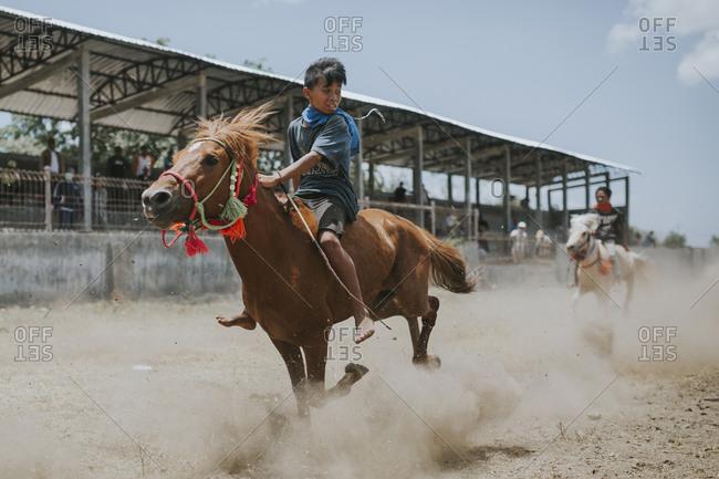 Indonesia, Sumbawa Besar - September 16, 2017: Jockey looking away while riding racehorse during horse racing