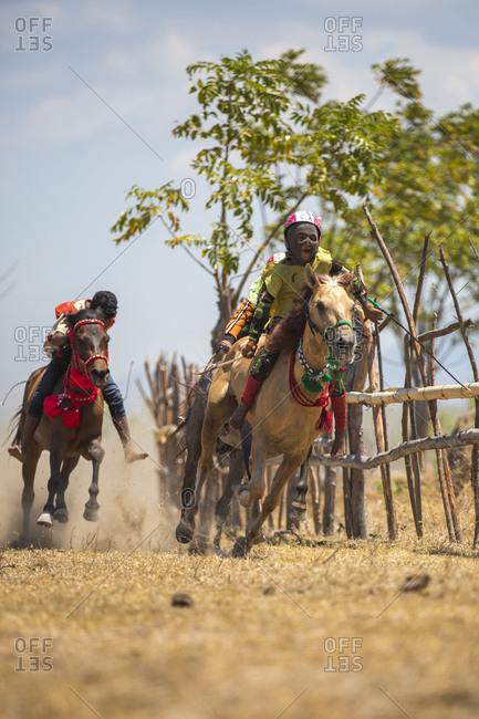 Indonesia, Sumbawa Besar - September 21, 2017: Child Jockeys riding racehorses on field during horse racing