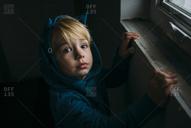 High angle portrait of cute boy wearing hooded shirt at home