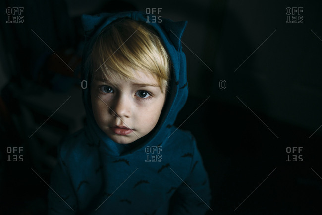 High angle portrait of cute boy wearing hooded shirt in darkroom