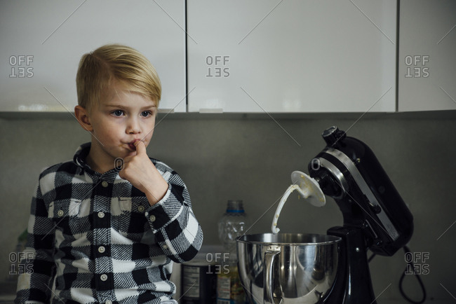 Cute boy tasting food from mixer in kitchen