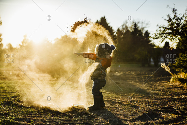 Side view of mischievous boy playing with soil at park