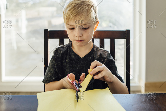 Boy cutting paper with safety scissors at home