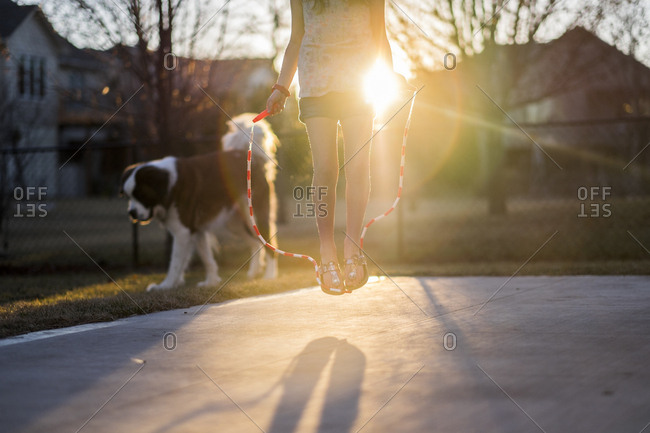 Low section of girl jumping rope at playground with dog in background