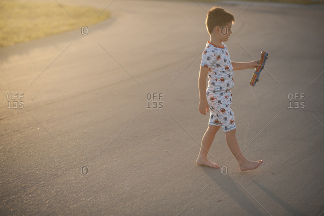 Side view of boy holding toy train while walking on road during sunset