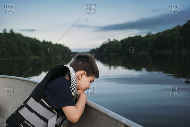 Side view of boy wearing life jacket while sitting in boat on lake