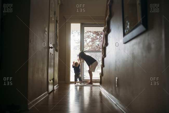 Siblings playing by door at home