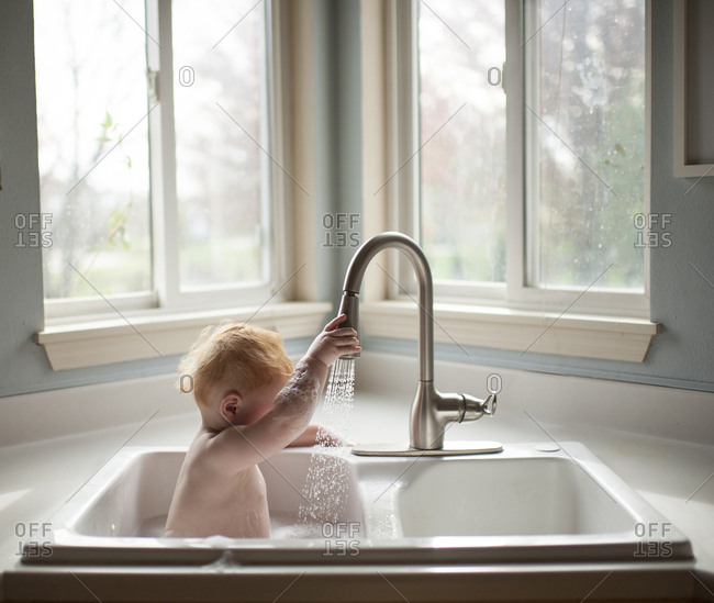 Cute baby boy holding faucet while sitting in kitchen sink against windows at home
