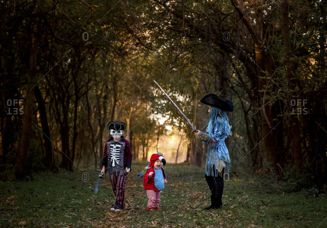 Siblings wearing Halloween Costumes while standing against trees at park
