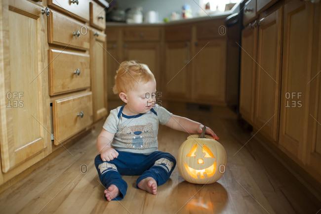 Cute baby boy with jack o' lantern sitting on floor in kitchen
