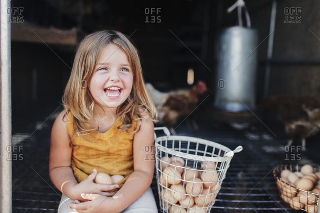 Cheerful girl sitting in animal pen