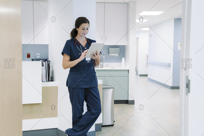 Female doctor using tablet computer while leaning against architectural column in hospital