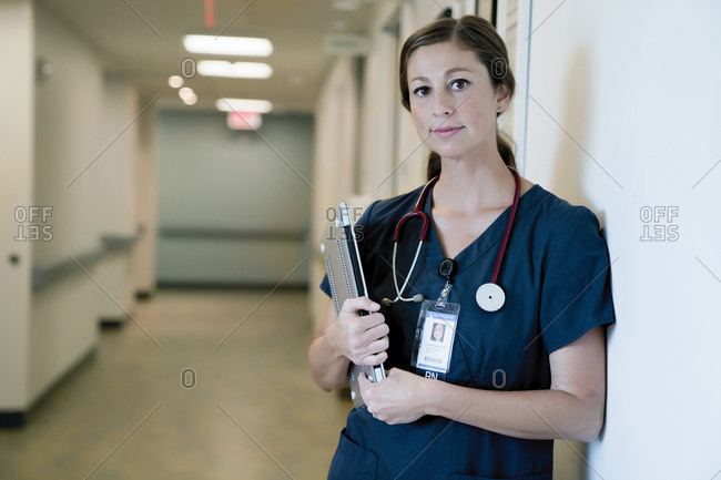 Portrait of confident female doctor holding laptop computer while standing in hospital lobby