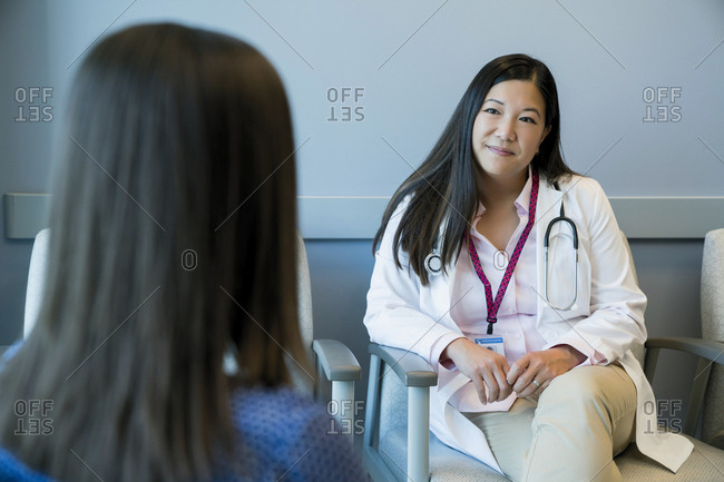 Female doctor looking at woman while sitting on chair in hospital waiting room