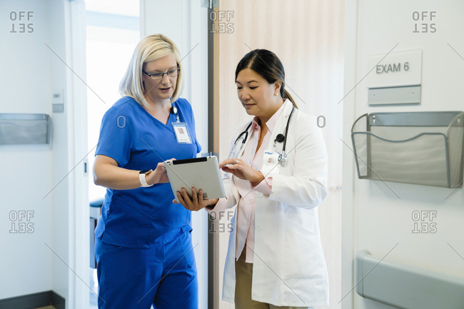 Female doctors discussing over tablet computer while standing by wall in hospital