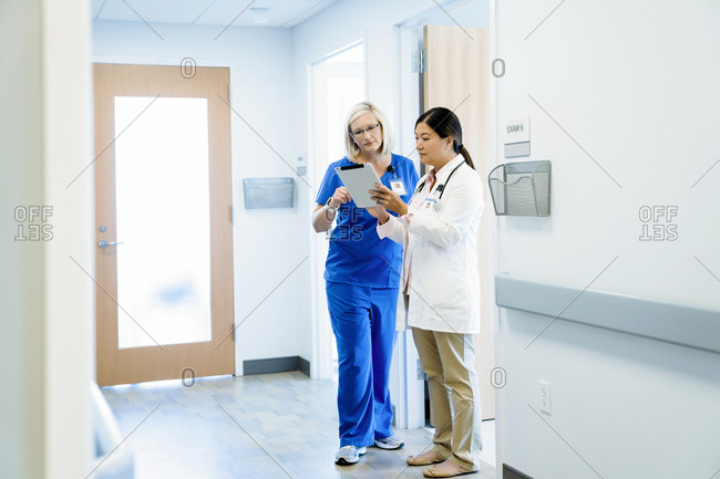 Female doctors discussing over tablet computer while standing in hospital corridor