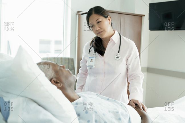 Female doctor looking at senior patient lying on bed in hospital ward