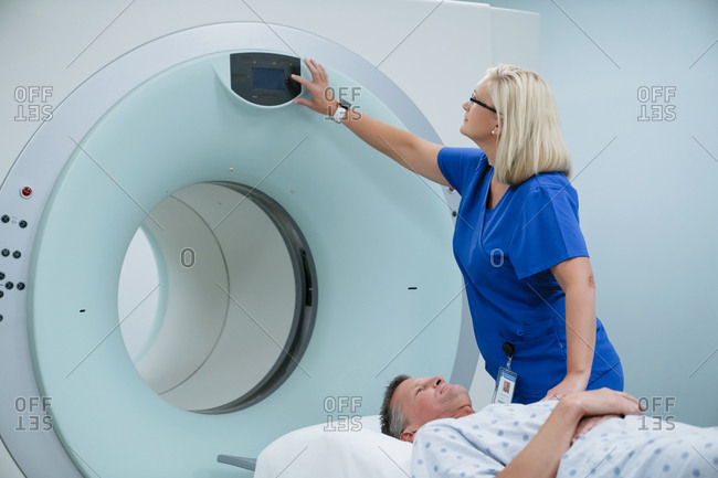 Nurse adjusting button on MRI Scanner while patient lying in examination room