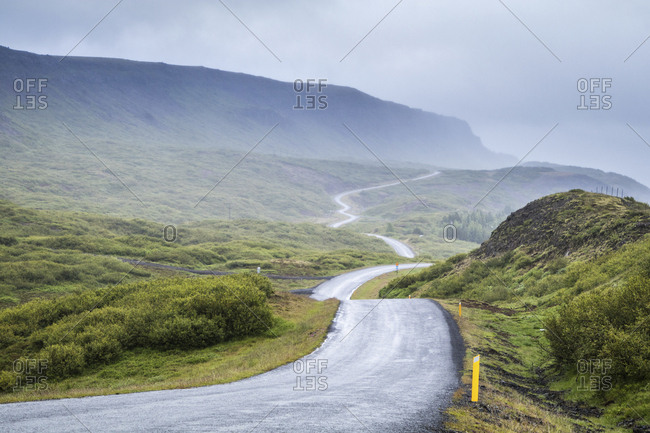 Winding road against mountains during foggy weather