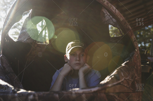 Thoughtful boy with hands on chin looking away in tent during sunny day