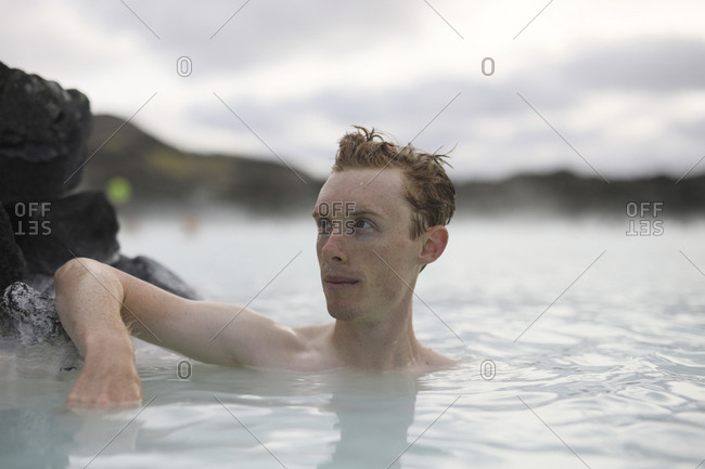 Thoughtful tourist looking away while swimming in hot spring