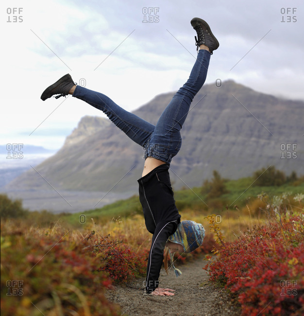 Excited female hiker doing handstand on field against mountains