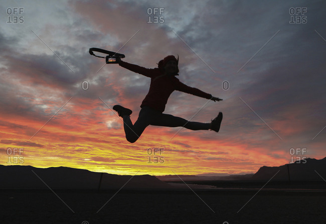 Excited hiker holding camera while jumping against dramatic sky
