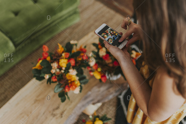 High angle view of florist photographing bouquet with smart phone at store