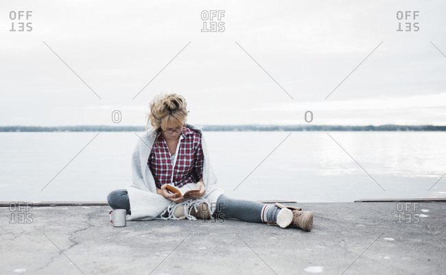 Full length of woman reading diary while sitting at lakeshore against sky